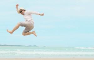 Man jump happy during vacation at sea beach of Thailand